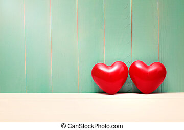 Red shiny hearts on vintage teal wood - Two red shiny hearts...