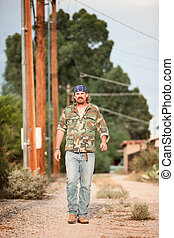 Man in camoflauge walking on dirt road - Rugged man in...