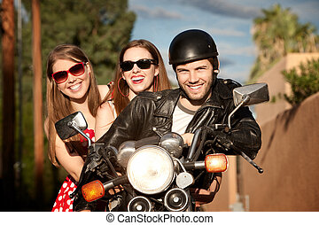 Trio posing on motorcycle - Three young adults posing on...