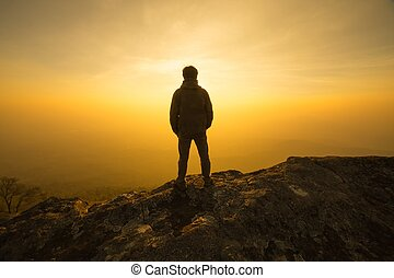 silhouette man standing into sunset