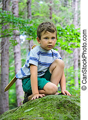 Boy with sword on a walk in the park.