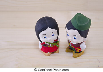 Toy boy and girl in Serbian national wear on a wooden table