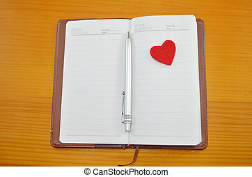 Notebook and a small red heart on a table - Notebook, pencil...