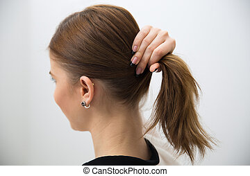 Side view portrait of a woman holding her hair