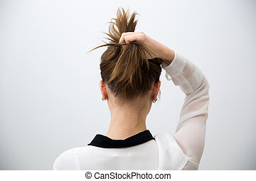 back view portrait of a woman holding her hair