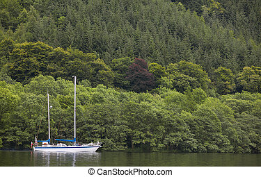 Caledonian canal with sailboat and forest in Scotland....