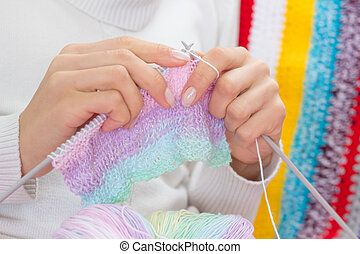 Knitting multicolored scarf - Woman knitting multicolored...