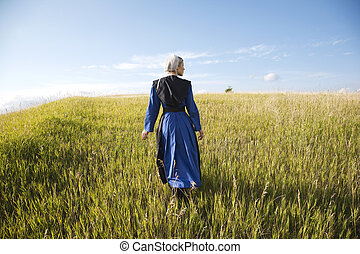 Amish woman in blue dress and black cape in field - An Old...