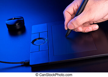mans hand draws on graphic tablet in blue light
