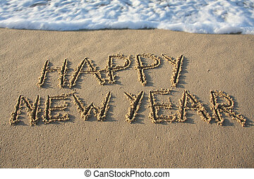 Happy new year written in the sand.