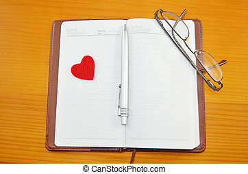 Notebook, pencil and a small red heart on a table -...
