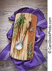 old spoon on a cutting board and fresh sprigs of rosemary on...