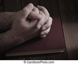 prayer - tie palms with cross fingers closeup on the Bible...
