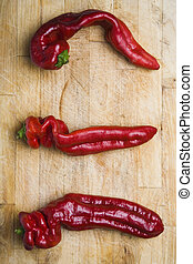 Three Chilis - Three red chili peppers on a wooden chopping...