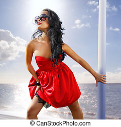 beautiful woman in red dress on the shore
