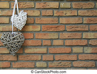 Heart ornaments. - Two woven wicker hearts hang on a brick...