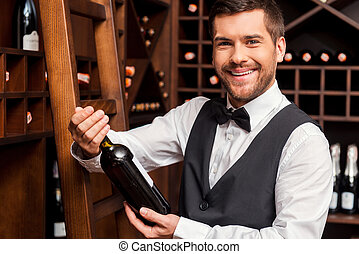 Confident sommelier. Confident male sommelier holding wine bottle and smiling while standing near the wine shelf
