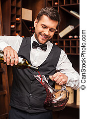 Pouring wine to decanter Confident male sommelier pouring...