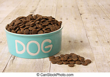 Dog food in a bowl. - Bowl with dog food on a hardwood...