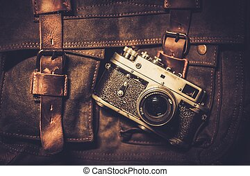 Vintage camera and handbag on wooden background