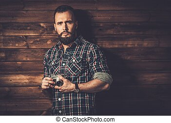 Man with beard in checkered shirt holding camera