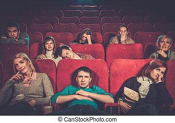 Group of people watching boring movie in cinema
