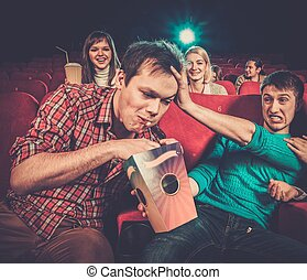 Impudent young man steals popcorn in cinema while people...