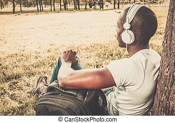 Smiling young african american man listens music in a park