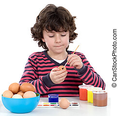 Child adorable adorning Easter eggs on a white background