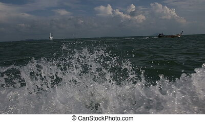 longtail thai motor boat floating on sea waves in the sea...