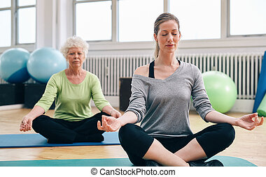 Women doing yoga in class - Two women practicing yoga in...