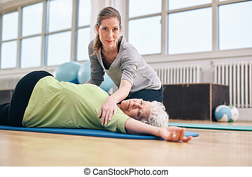Trainer helping senior woman in her stretching workout -...