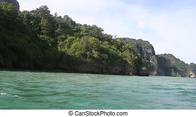 boat sailing past cliff island shore - longtail thai motor...
