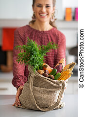 Closeup on young housewife showing fresh vegetables in...