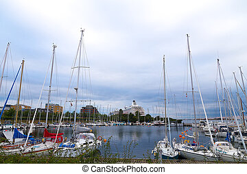 Docking yachts against the grey skies. A small marina with yachts in the harbor of Copenhagen Denmark