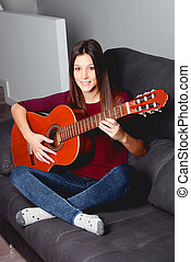 Pretty girl playing guitar on the couch
