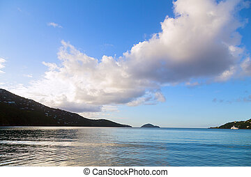 A scenic sunset on a tropical island. Quiet ocean waters reflect the lights of sunset in the Magens Bay, the US Virgin Islands.