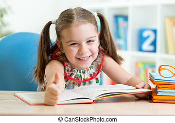child girl reading story from big book in nursery - Cute...