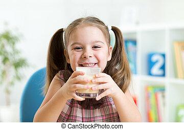 little girl drinking milk from glass indoor - child girl...