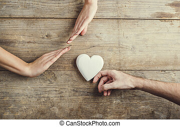 Man offering a heart to a woman. - Man offering a white...