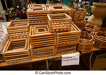 Wooden orchid baskets for sale - A sales table of orchid...