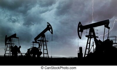 oil pumps silhouette against the background of Thunderstorm...