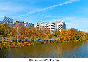 Rosslyn scenic skyline and Potomac river bank in autumn. Office buildings viewed from Theodore Roosevelt Bridge, Washington DC.
