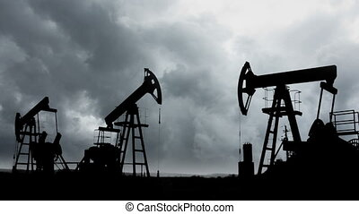 oil pumps silhouette against the background of storm clouds...