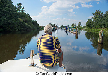 Man on boat - Man sitting on boat near sluice in Holland
