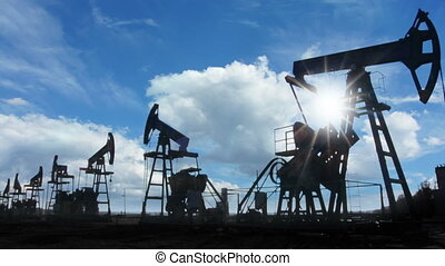 working oil pumps silhouette against timelapse clouds
