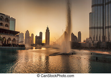 Dubai lagoon with fountain against sunset in UAE - Dubai...