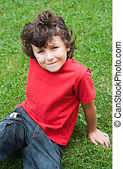 Happy child sitting on the grass