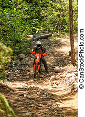 Dirt Bike Rider - Man riding a dirt bike along a rocky trail...