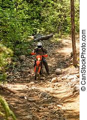 Dirt Bike Rider - Man riding a dirt bike along a rocky trail...